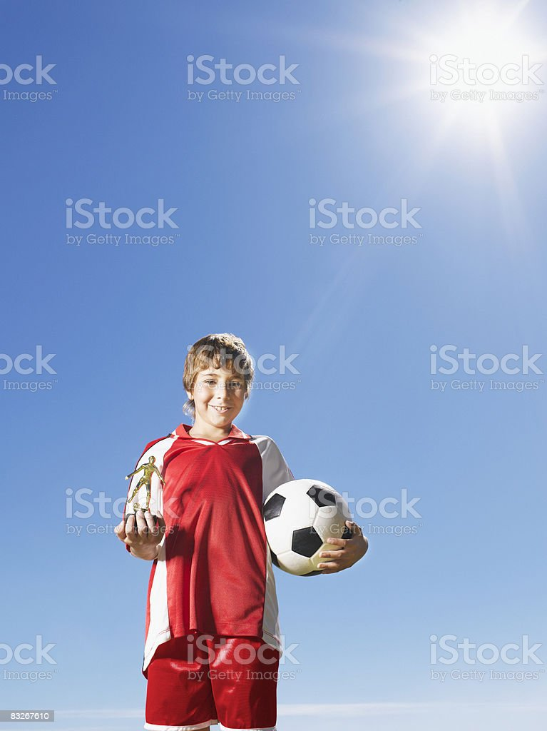 Boy in uniform holding trophy and soccer ball stock photo
