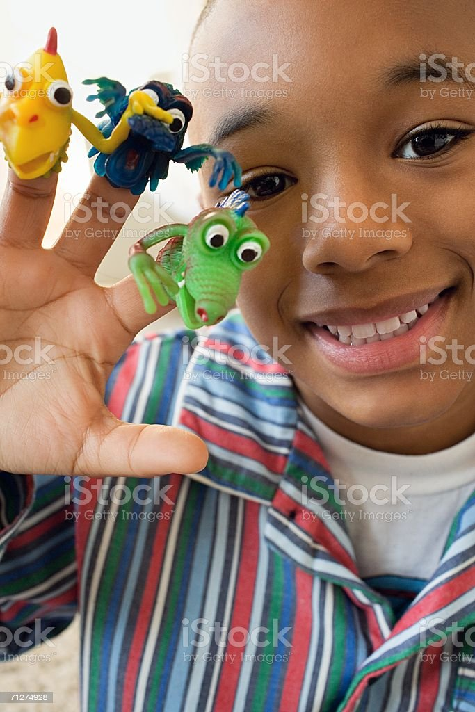 Boy indoors with monster finger puppets on fingers stock photo