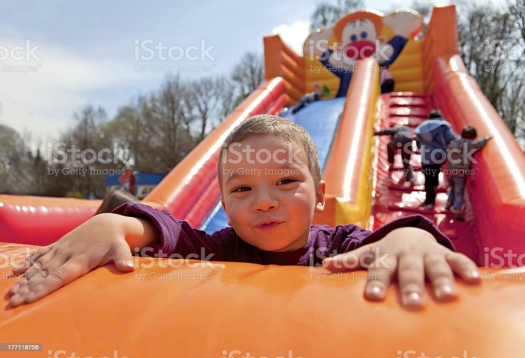 Boy inflatable slide stock photo