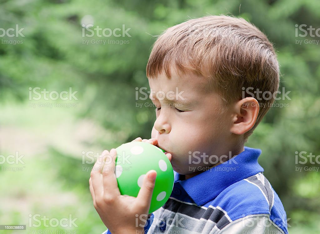 Boy inflates  balloon in park royalty-free stock photo