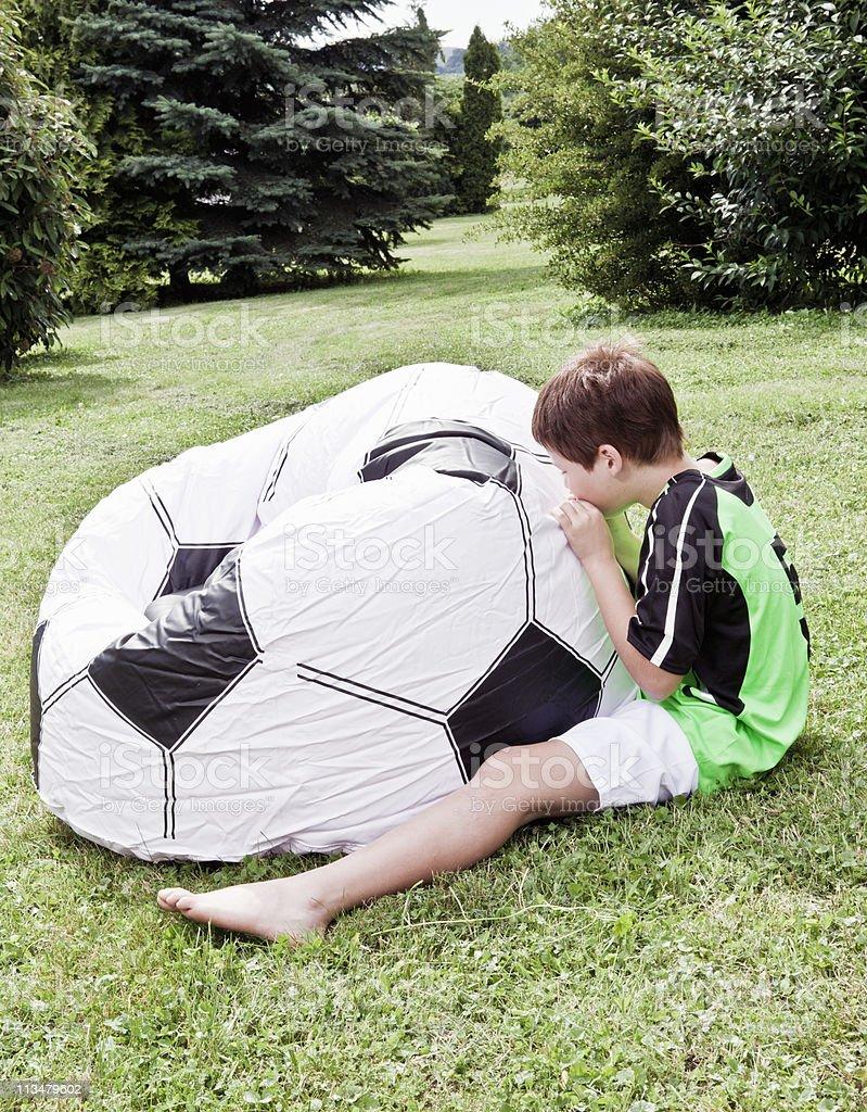 Boy inflating giant football stock photo