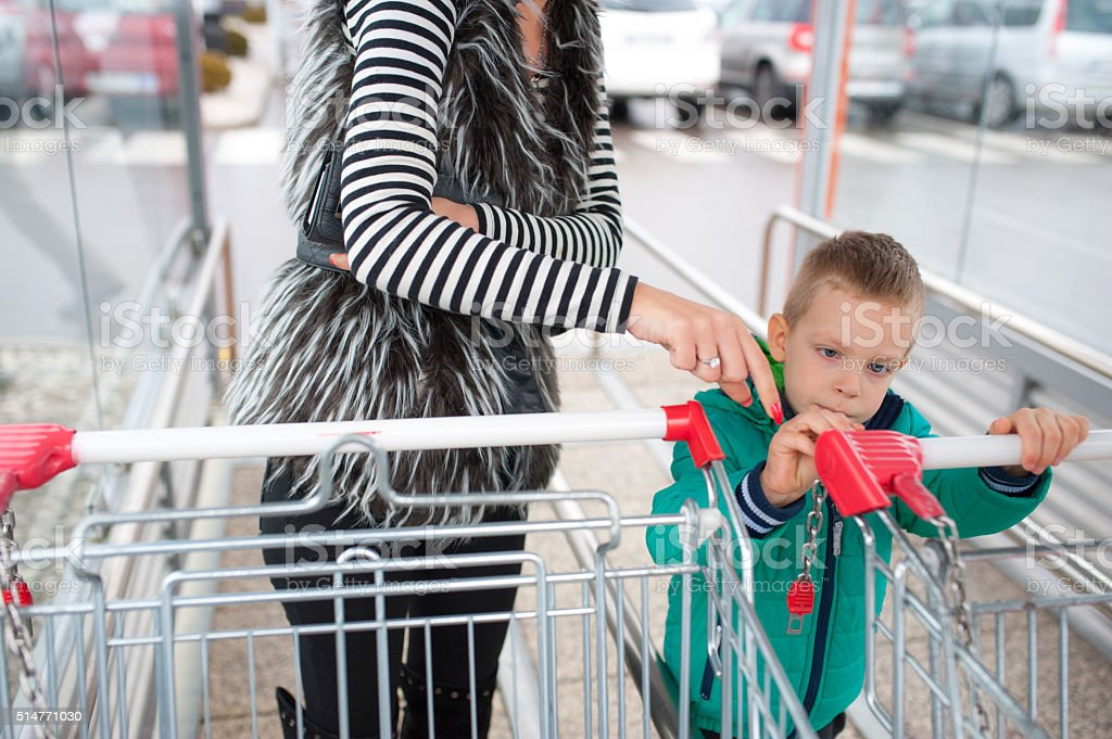 Boy Inserting Coin or Token in Shopping Cart stock photo
