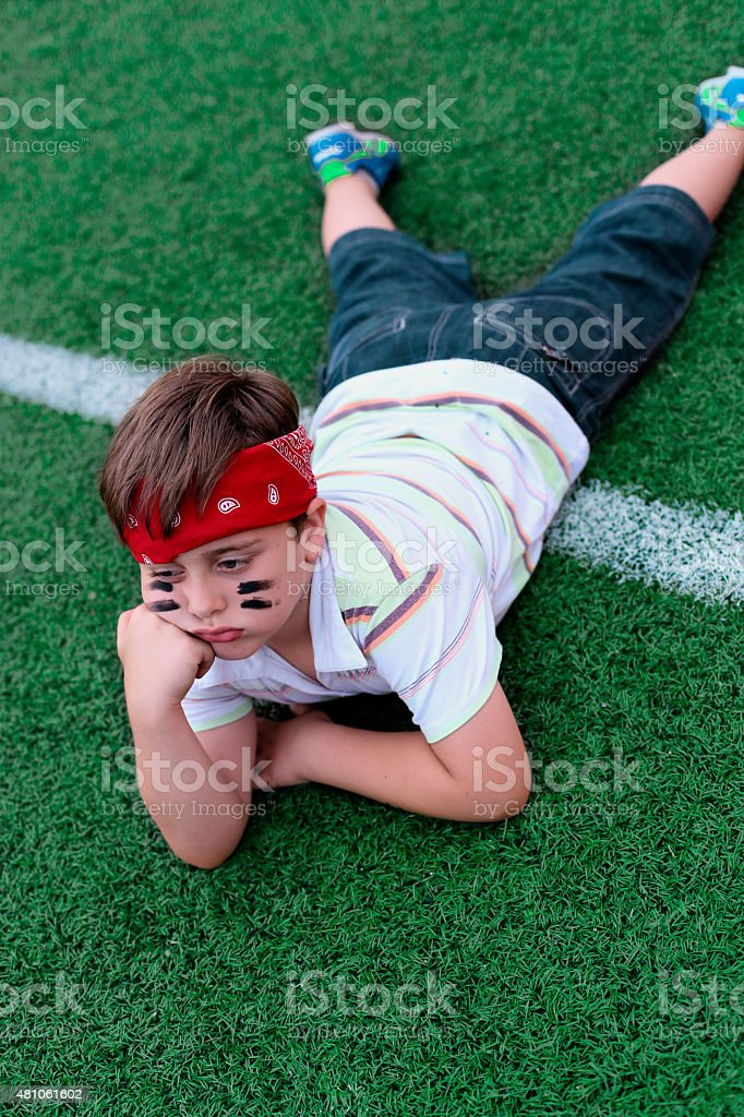 boy is bored at a football match stock photo