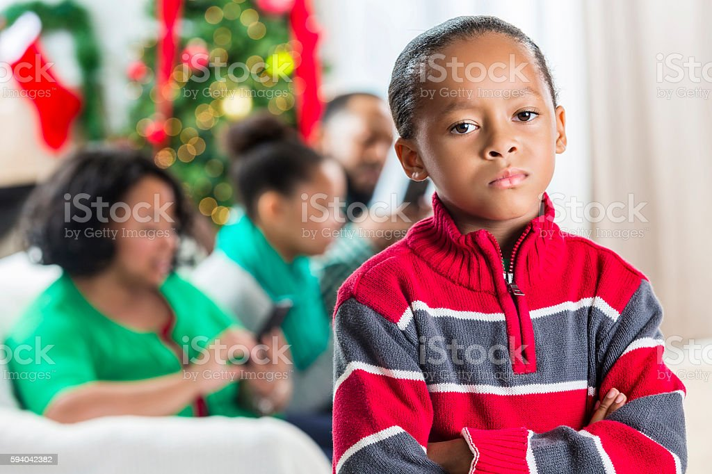Boy is concerned with family's use of technology at Christmastime stock photo