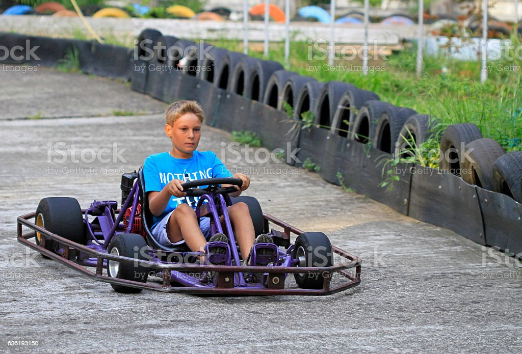 boy is driving a kart on circuit stock photo