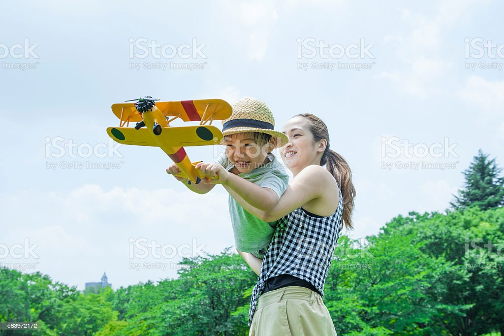 Boy is facing a mother playing with airplane stock photo
