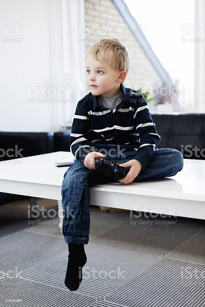 Boy is focused on playing video game royalty-free stock photo