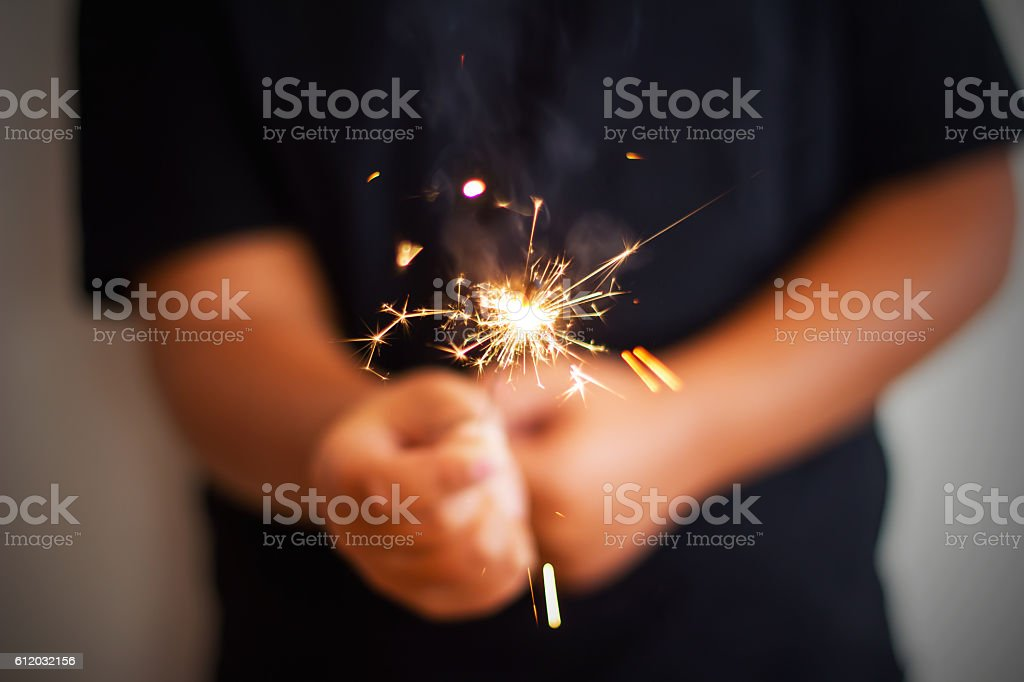 Boy Is Holding A Roman Candle For Birthday stock photo