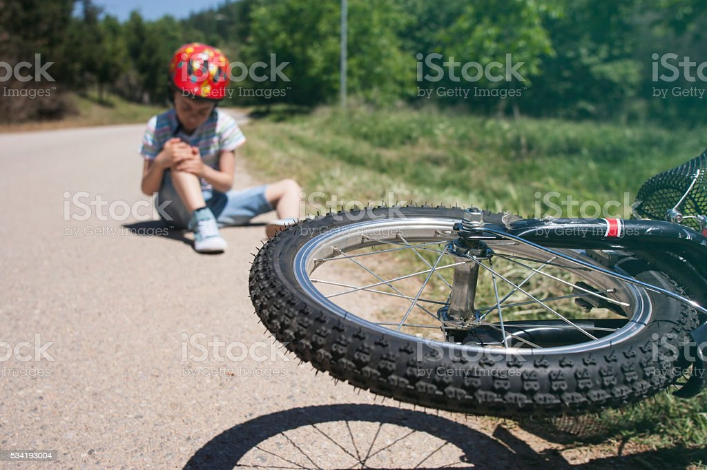 Boy is lying hurt after a bicycle accident stock photo