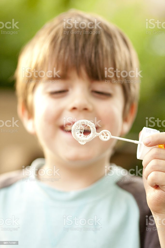 Boy is playing bubble wand stock photo