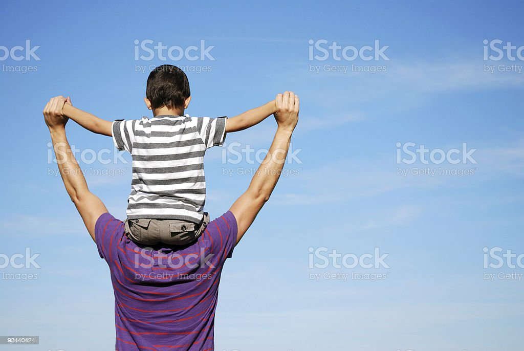 A boy is sitting up high on his dad's shoulders stock photo