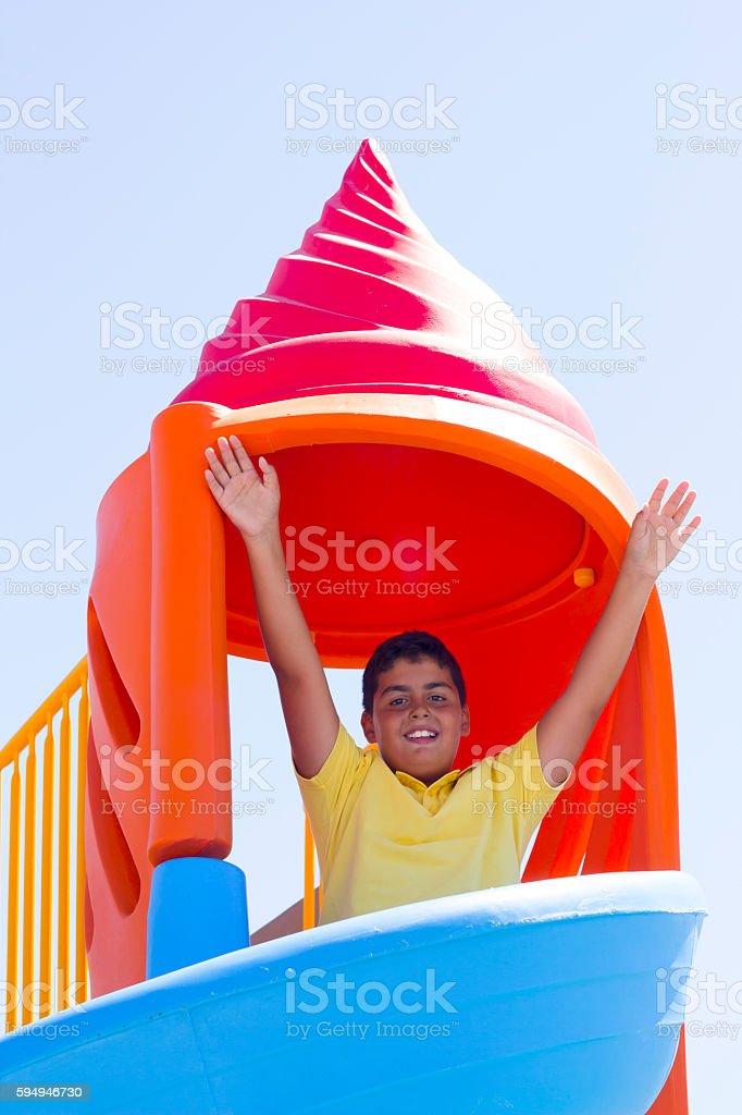 Boy Is Sliding Down The Slide stock photo