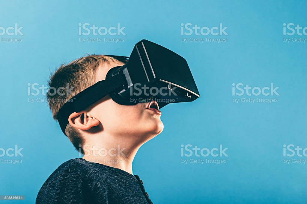 Boy is surprised by content on VR glasses stock photo