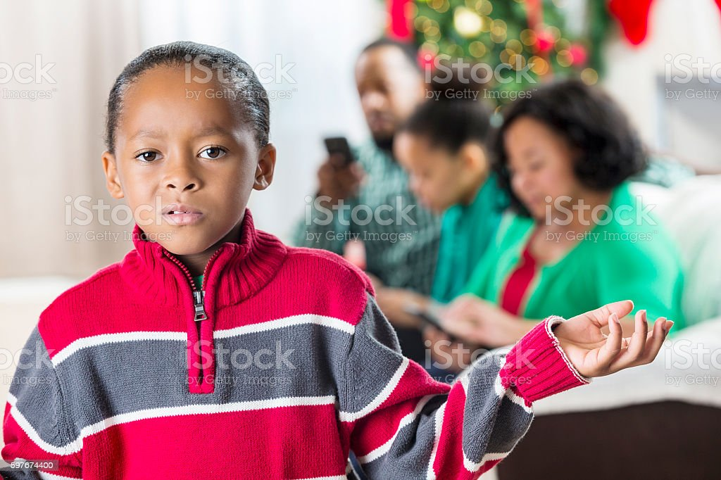 Boy is upset with family for using technology at Christmastime stock photo