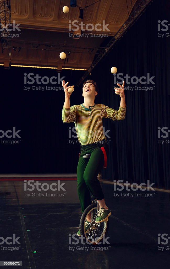 Boy juggling and riding unicycle stock photo