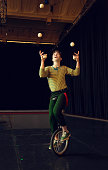 Boy juggling and riding unicycle