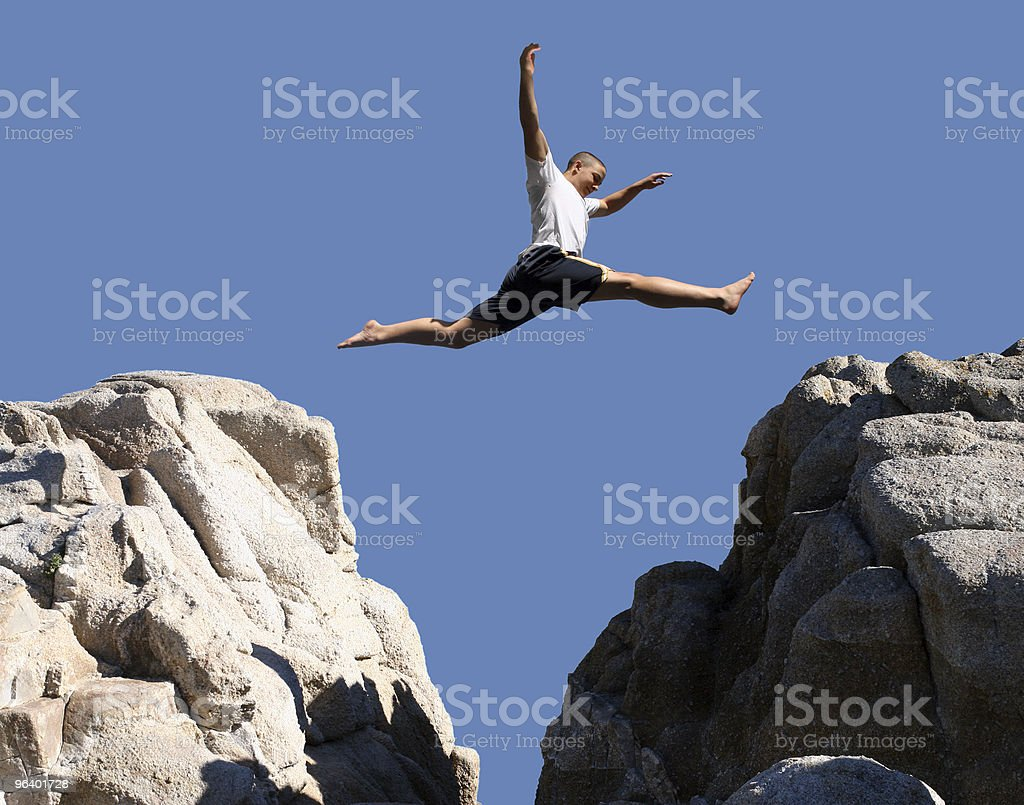 Boy jumping between two rock formations stock photo