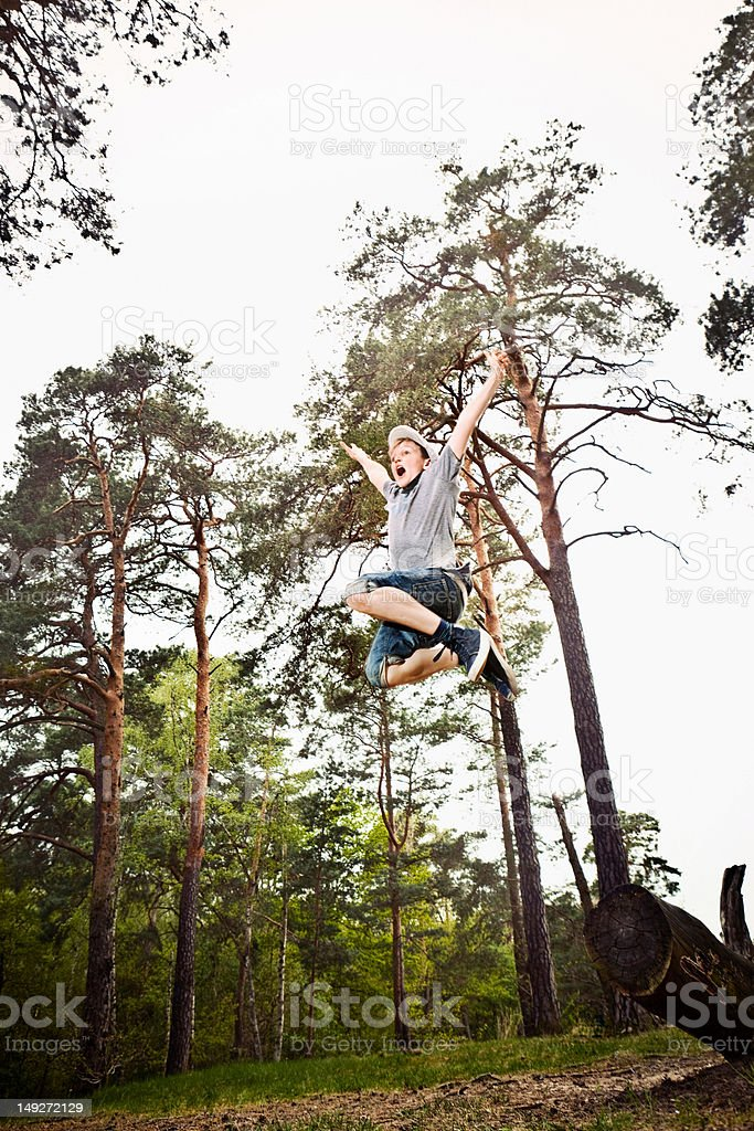 Boy jumping in forest stock photo