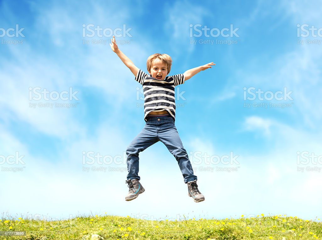 Boy jumping in meadow stock photo