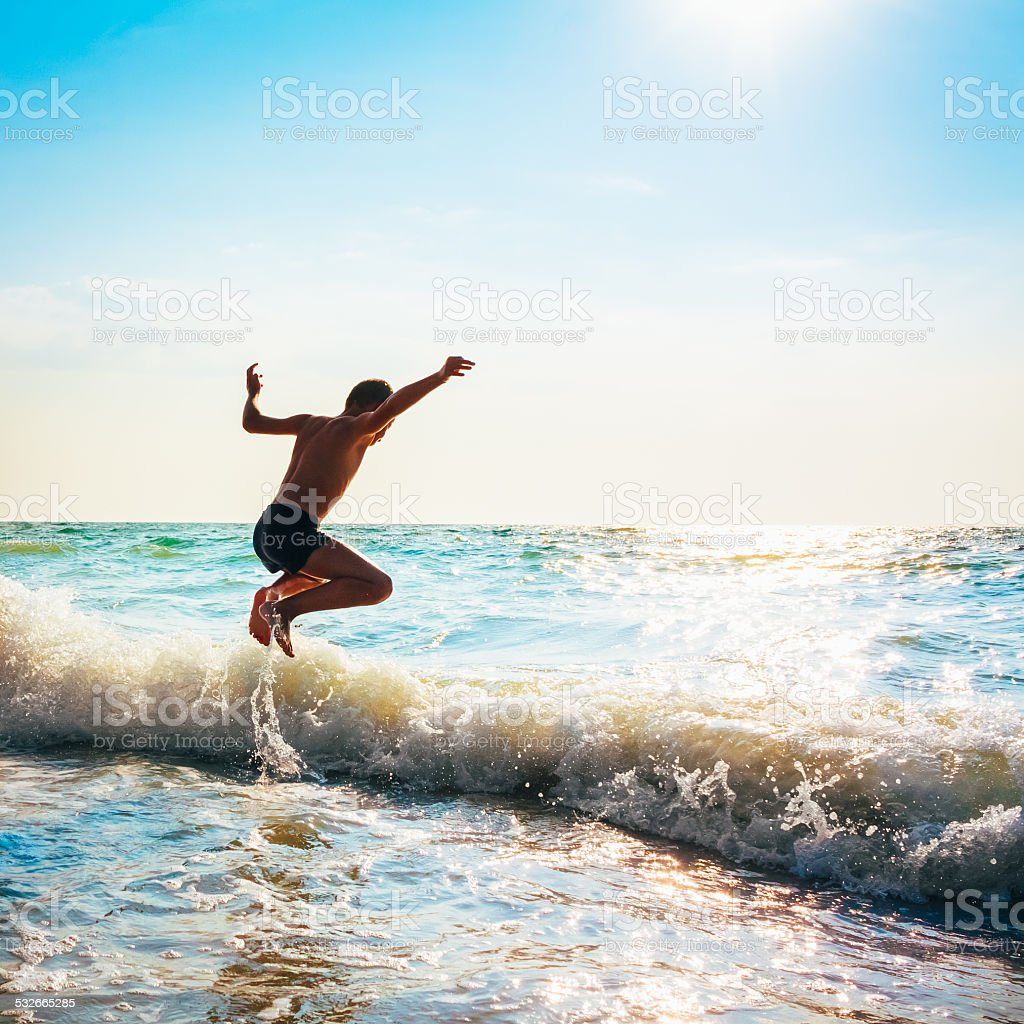 Boy Jumping In Sea Waves stock photo