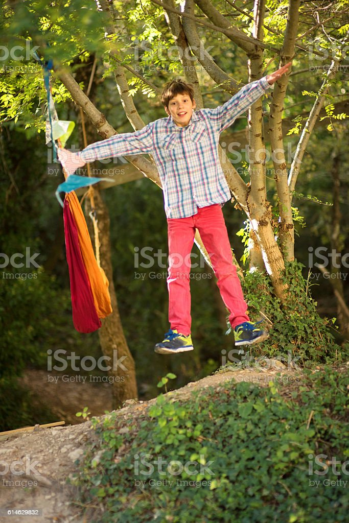 Boy jumping in the woods stock photo