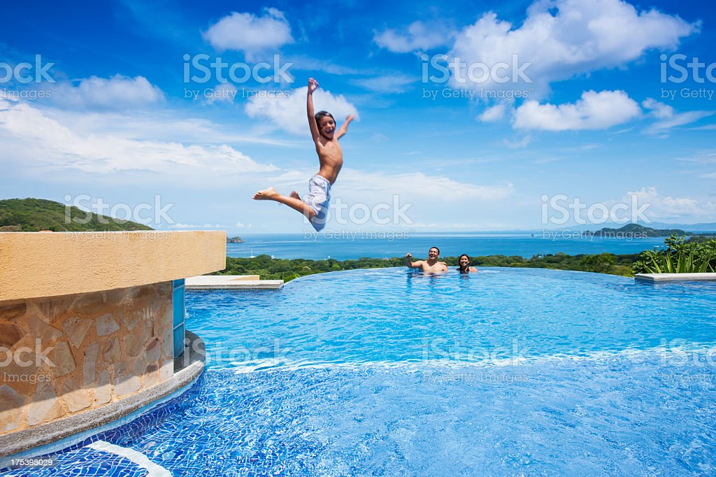 Boy jumping into a swimming pool in Costa Rica stock photo