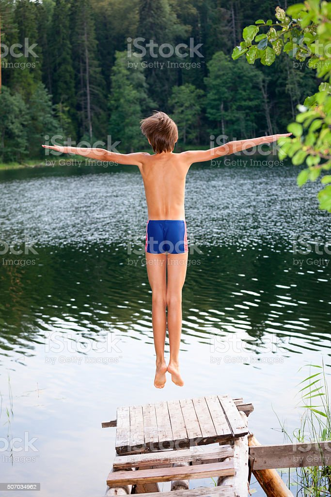 Boy jumping into forest lake stock photo