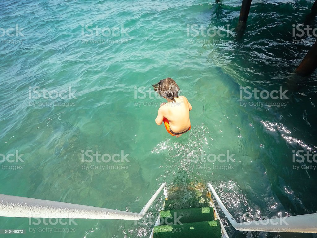 Boy jumping into the sea stock photo