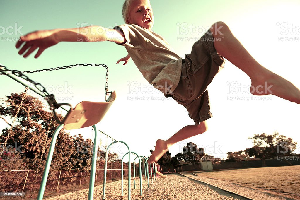 Boy Jumping off a Swing stock photo