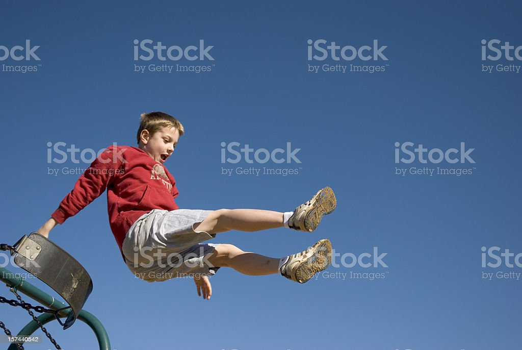 Boy Jumping Off Swing With Clear Blue Sky stock photo