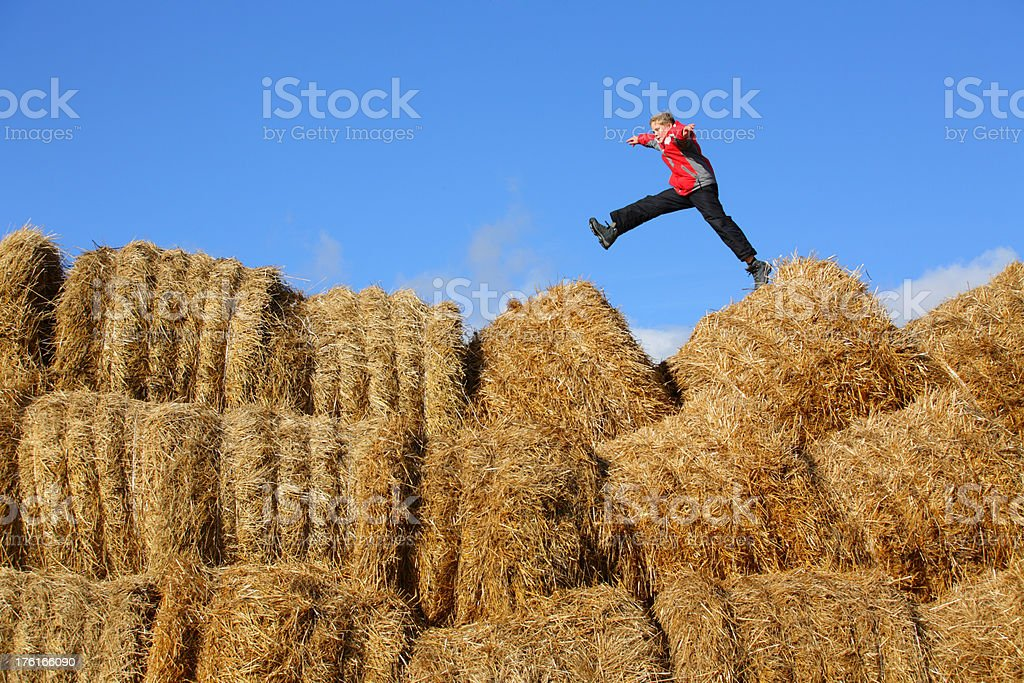 Boy jumping on a haystack stock photo