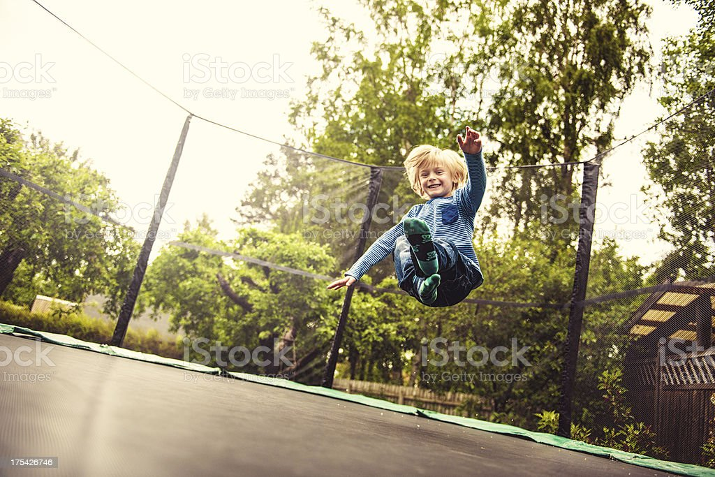 Boy jumping on a trampoline stock photo