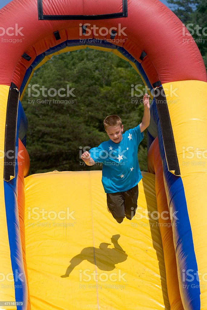Boy Jumping On An Inflatable Slide Midair. royalty-free stock photo