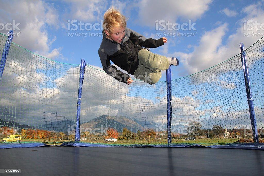 Boy Jumping on Trampoline stock photo