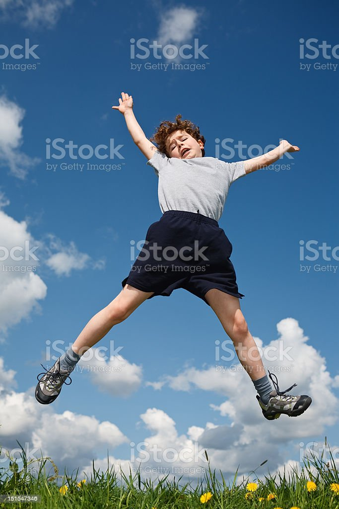 Boy jumping outdoor against blue sky stock photo