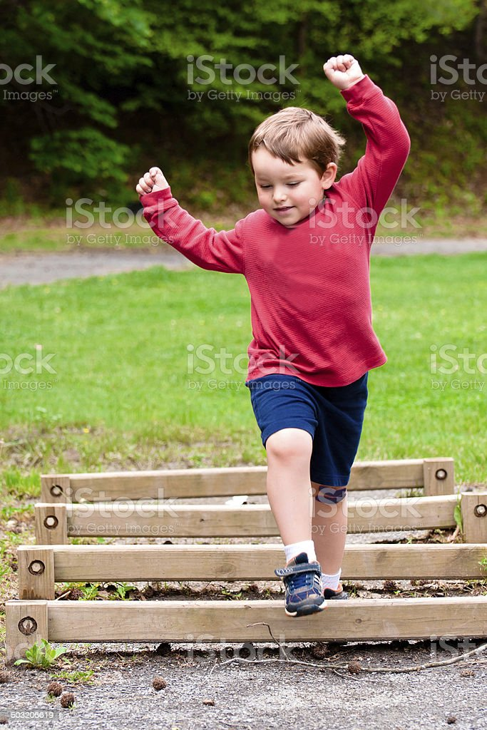 Boy jumping over obstacle on exercise course stock photo