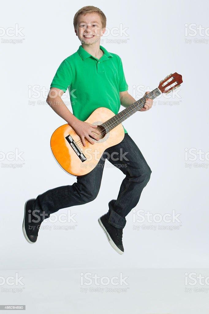 Boy jumping with a guitar stock photo