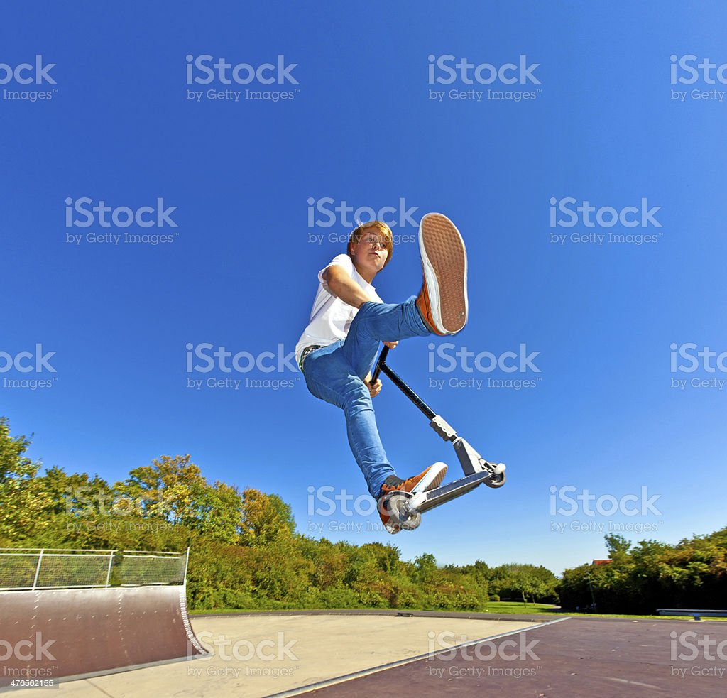 boy jumping with his scooter stock photo