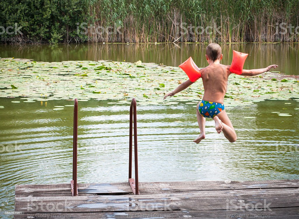 Boy jumps into the water stock photo
