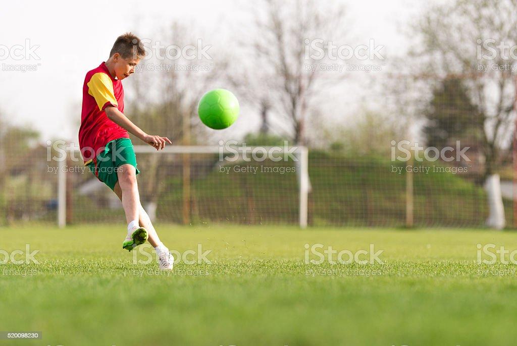 boy kicking a ball at goal stock photo