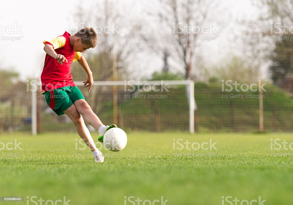 boy kicking a ball at goal stock photo