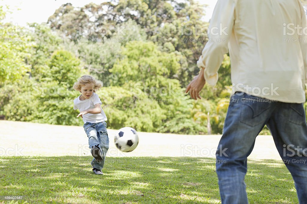 Boy kicking a football in his fathers direction stock photo