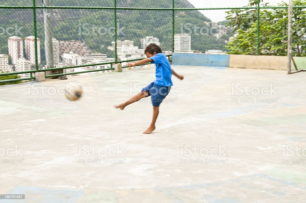 Boy Kicking A Football, Rio de Janeiro, Brazil, South America. royalty-free stock photo