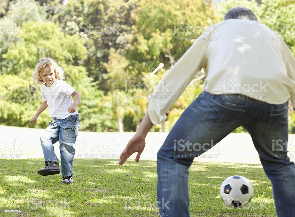 Boy kicking a football to his father stock photo