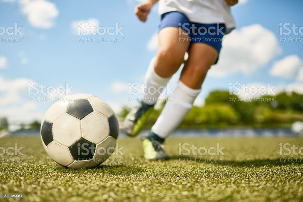 Low section portrait of unrecognizable teenage boy kicking ball...