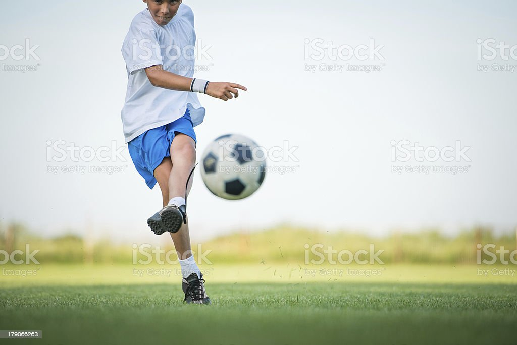 Boy kicking soccer ball while playing on the field stock photo