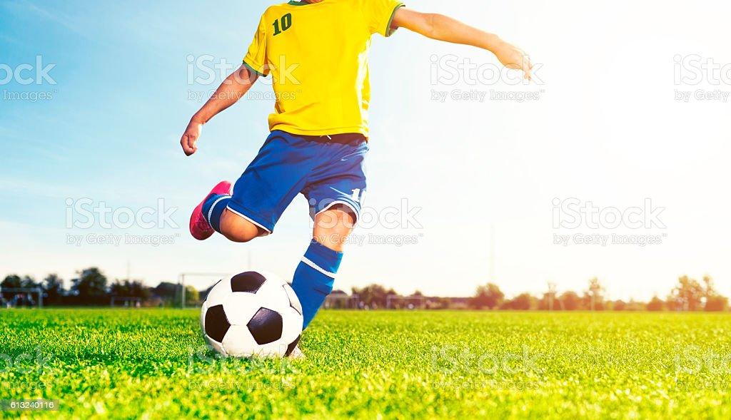 Boy kicks soccer ball while playing a football match stock photo