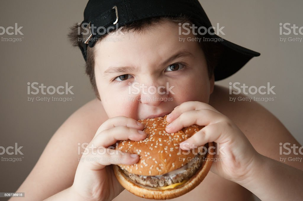 boy kid fat  burger food  health sports cap hungry stock photo