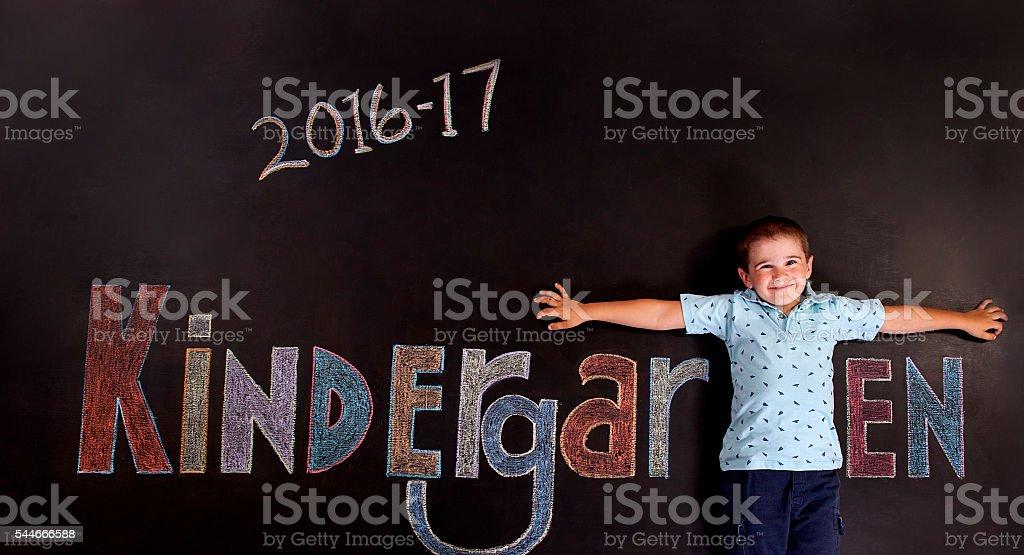 Boy Kindergartener on chalkboard stock photo