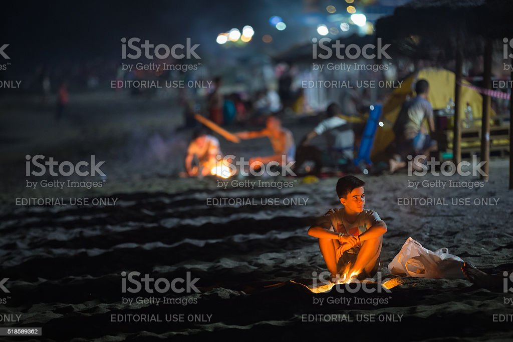 Boy kindles a fire during Sant Joan holiday in Spain stock photo